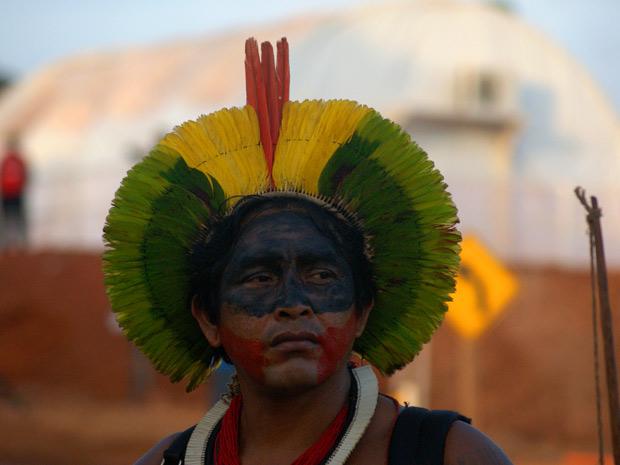 Indígena com arco e flecha em frente a canteiro ocupado (Foto: Divulgação/Ivan Canabrava/ Illuminati filmes)