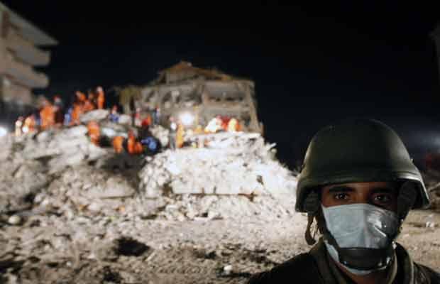 Soldado monta guarda durante trabalhos de resgate nos escombros de prédios na cidade turca de Ercis nesta quarta-feira (26) (Foto: AP)