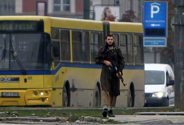 Homem armado caminha nesta sexta-feira (28) em Sarajevo após disparar contra a Embaixada dos EUA (Foto: Reuters)