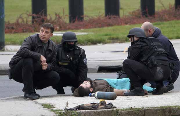 Atirador caído após ser atingido por policial nesta sexta-feira (28) em Sarajevo, na Bósnia (Foto: Reuters)