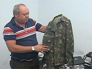 Policial mostra farda apreendida em Campina Grande (PB) (Foto: Reprodução/TV Paraíba)