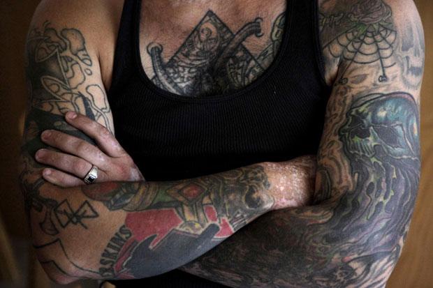 Tatuagens nos braços de Widner ainda existem, mas podem ser cobertas por uma manga longa. Ele pretende cobrir com novas tatuagens aquelas que têm contexto político ou racista (Foto: Jae C. HongAP)