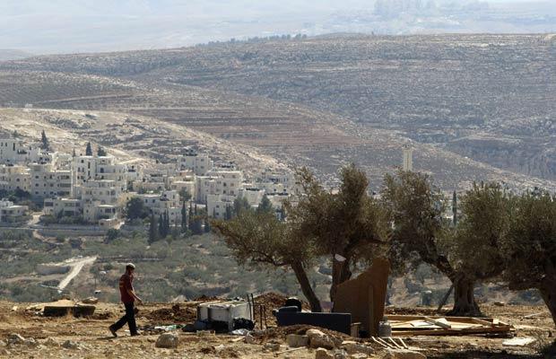 Colono israelense anda próximo a escombros de estrutura destruída pelo Exército de Israel em Ramat Migron, próximo a Ramallah, na Cisjordânia, nesta terça-feira (1º) (Foto: AP)