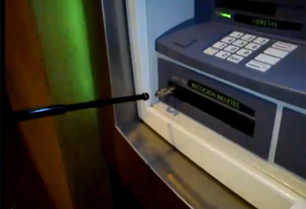Apesar dos ataques da cobra, homem conseguiu sacar o dinheiro. (Foto: Reprodução/YouTube)