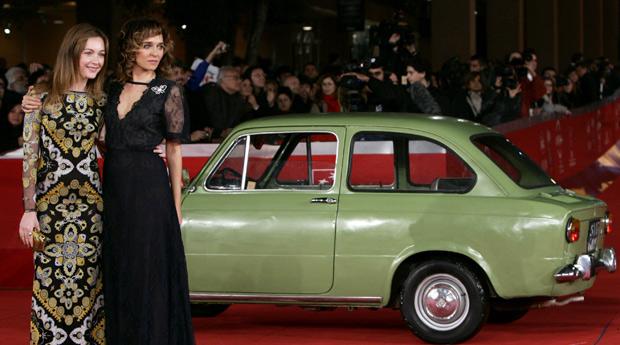 A atriz italiana Cristiana Capotondi (esq.) também aproveitou a presença do carrinho, fabricado entre 1964 e 1973, para fazer pose (Foto: Riccardo De Luca/AP)