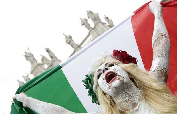 Manifestante do grupo ucraniano Femen, com bandeira da Itália, participa de protesto contra o governo Berlusconi, em Roma, no sábado (5) (Foto: Reuters)