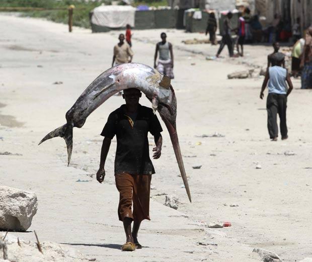 Um pescador foi flagrado na sexta-feira (4) carregando um peixe sobre a cabeça em Mogadíscio, na Somália.  (Foto: Feisal Omar/Reuters)