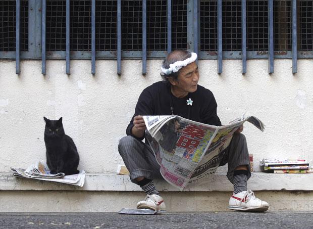 Gato parece ler jornal ao lado de dono (Foto: Shizuo Kambayashi/AP)