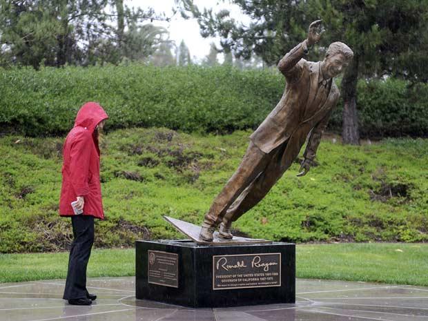Mulher observa a estátua danificada de Ronald Reagan neste domingo (6) em Newport Beach, na Califórnia (Foto: AP)