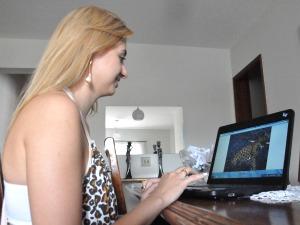 Viviane mostra imagens que fez de onça no Pantanal de MS (Foto: Ricardo Campos Jr. / G1 MS)