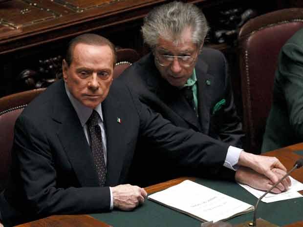 O premiê da Itália, Silvio Berlusconi, segura a mão do ex-aliado Umberto Bossi nesta terça-feira (8) durante votação no Parlamento em Roma (Foto: Reuters)