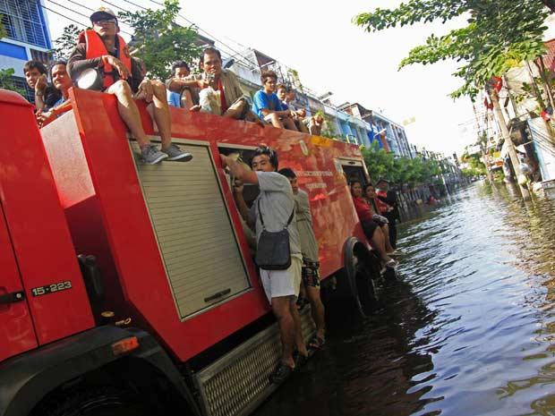 Caminhão de bombeiros retira moradores de área alagada em Bangcoc nesta terça-feira (8) (Foto: AP)