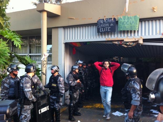 Estudante deixa a reitoria da USP, cercada por PMs do Choque (Foto: Juliana Cardilli/G1)
