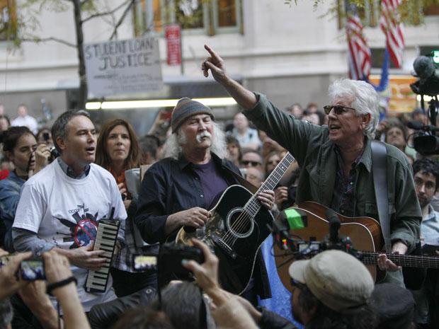 """O cantor David Crosby (ao centro), da banda Buffalo Springfield, canta com manifestantes do movimento """"Ocupe Wall Street"""" na praça Zucotti, em Nova York, nesta terça-feira (8). Celebridades como o rapper Kanye West, o cineasta Michael Moore e o ator Tim Robbins já visitaram o local. Centenas de pessoas estão acampadas há pouco menos de um mês em protesto contra o capitalismo em Wall Street (Foto: Mary Altaffer / AP)"""