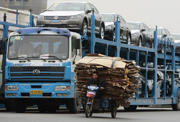 Triciclo lotado com papel divide espaço com caminhão-cegonha. (Foto: Sean Yong/Reuters)