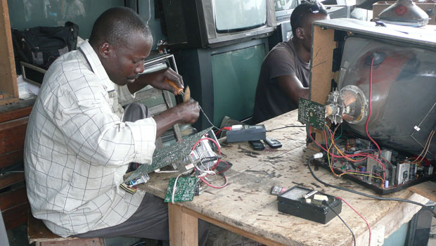 Homem conserta uma televisão quebrada em Cotonou, no Benin (Foto: Empa – ewasteguide)