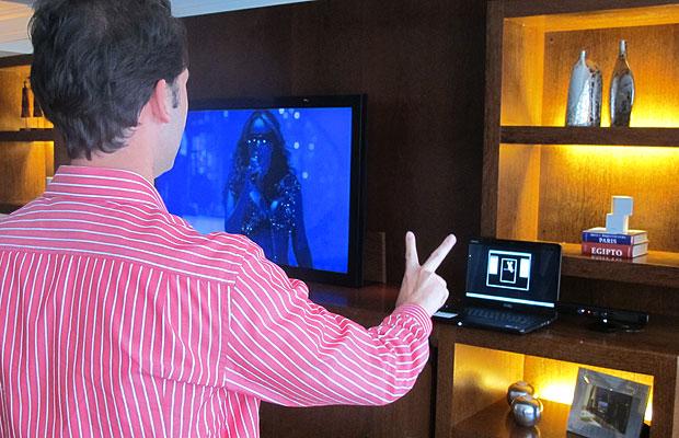 Gabriel Domingos mostra que, ao mostrar dois dedos para a câmera infravermelha, a TV pausa o filme (Foto: Laura Brentano/G1)