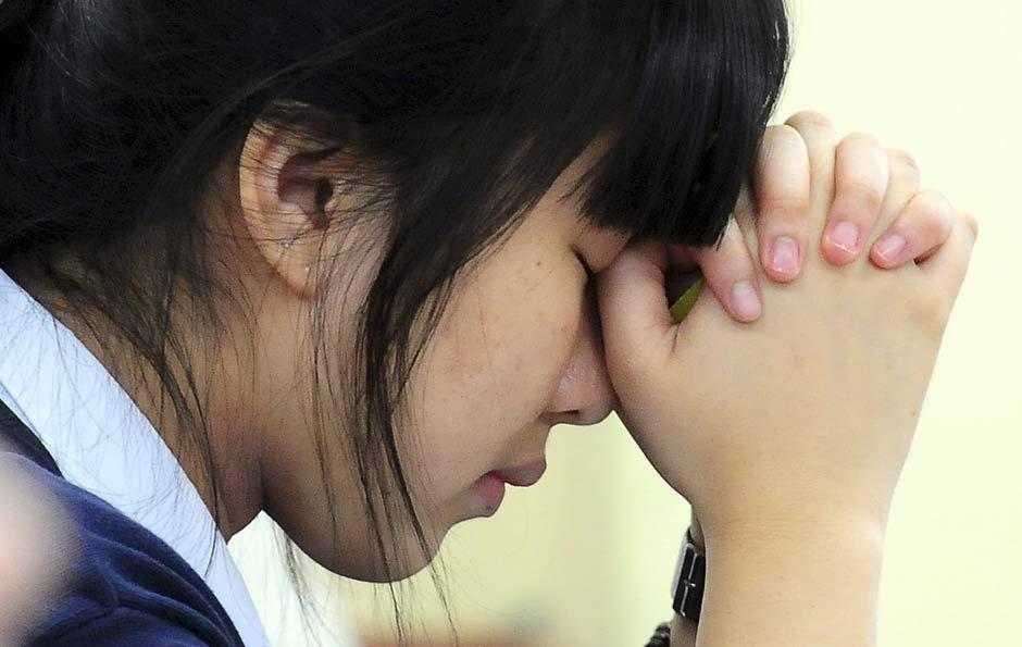 Estudante faz orações antes do início de vestibular em Seul, na Coreia do Sul.