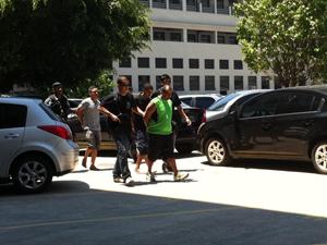 Preso é levado para carro da polícia após exame de corpo de delito (Foto: Thamine Leta/G1)