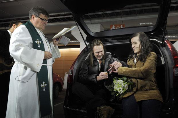 O noivo Juha-Ville Salin coloca a aliança na mão da amada, Merle Saksman, em casamento celebrado em um estacionamento de Helsinki (Foto: Reuters/Vesa Moilanen/Lehtikuva)