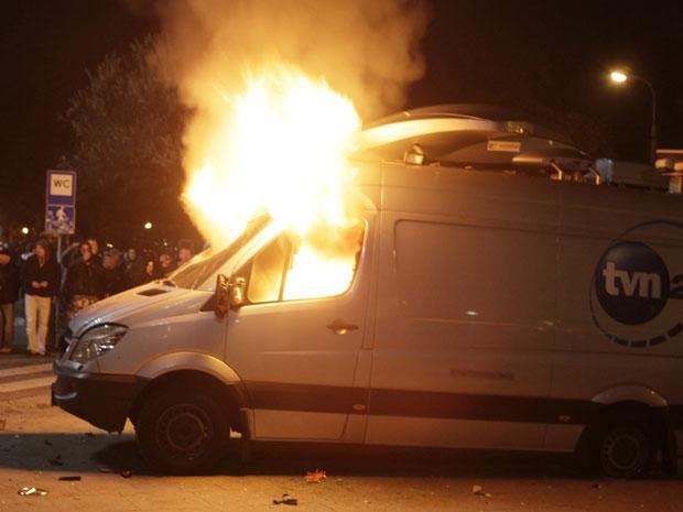 Manifestantes extremistas incendeiam o carro de uma emissora de TV durante um protesto violento no Dia da Independência da Polônia, em Varsóvia, nesta sexta-feira (11). (Foto: Czarek Sokolowski / AP)