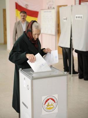 Mulher lança o seu voto em Tskhivali, neste domingo (13) (Foto: MIKHAIL MORDASOV/AFP)
