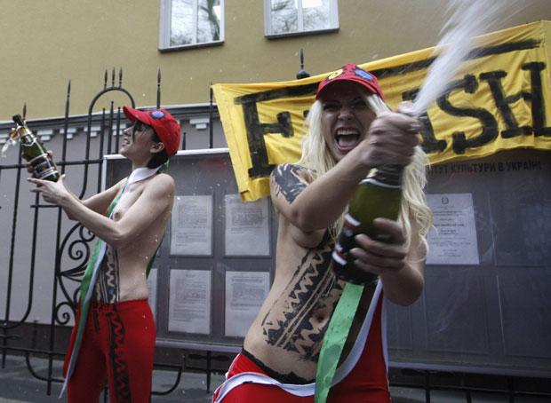 Com os seios à mostra e estourando garrafas de champagne, elas comemoraram em clima de 'fim de corrida' a substituição do premiê, ocorrida no final de semana após ficar claro que ele não possuía mais maioria em meio à situação de crise econômica que o país enfrenta. (Foto: Vladimir Sindeyev/Reuters)