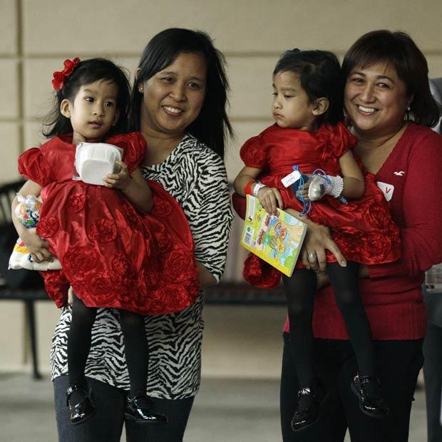 Angelina Sabuco, no colo da mãe, Ginady (à esq.), e Angelica, no colo da tia Marita, nesta segunda-feira (14) no hospital em Stanford, na Califórnia (Foto: AP)