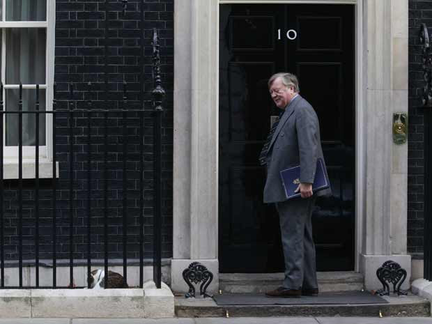 O secretário da Justiça britânico, Kenneth Clarke, observa Larry, o gato oficial do premiê britânico, dormindo do lado de fora da residência oficial, em 10 Downing Street, nesta terça-feira (15). Larry vem sendo alvo de 'criticas' dos tabloides britânicos por conta de sua suposta ineficiência na tarefa de caçar ratos na casa. Segundo fontes da residência oficial, ele passaria mais tempo dormindo que trabalhando (Foto: Reuters)