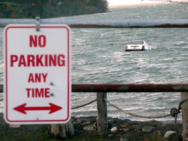 O carro de Conrardy é visto ao fundo, sendo lentamente engolido pelo mar na costa de Washington. À frente, uma placa indica que é proibido estacionar no local (Foto: Celene Wendt/AP)