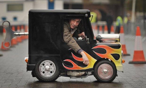 Perry Watkins transformou um brinquedo infantil no menor carro do mundo. (Foto: Ben Stansall/AFP)
