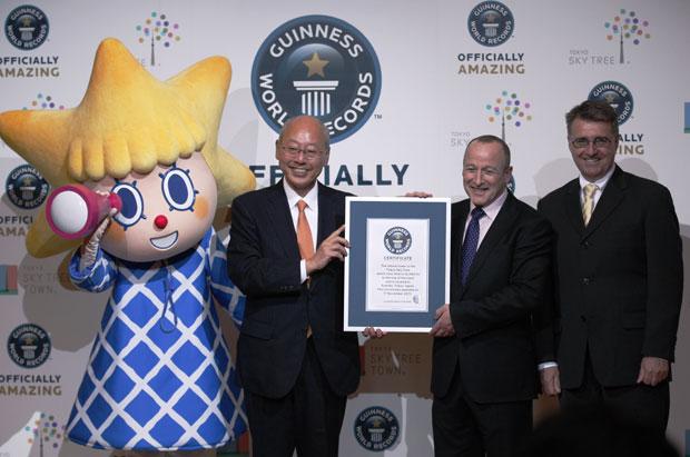 Mascote da torre posa ao lado do presidente da companhia dona da Tokyo Sky Tree durante cerimônia em que foi entregue o certificado do Guinness (Foto: Hiro Komae/AP)