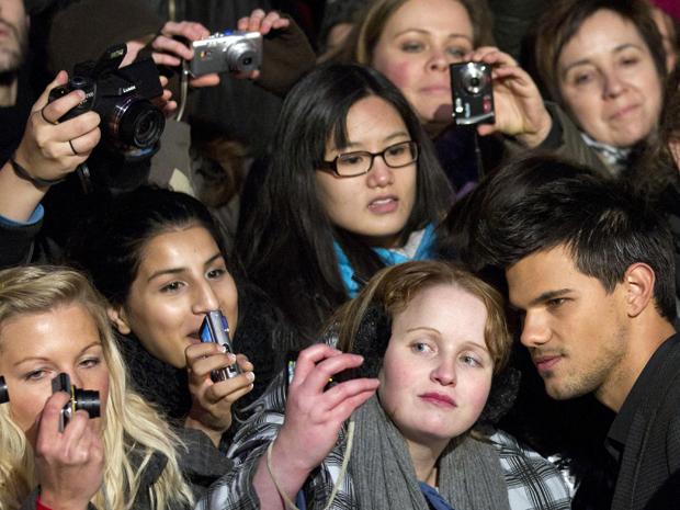 Taylor Lautner posa com fãs na Alemanha durante estreia do filme 'Amanhecer - parte 1' (Foto: Reuters)