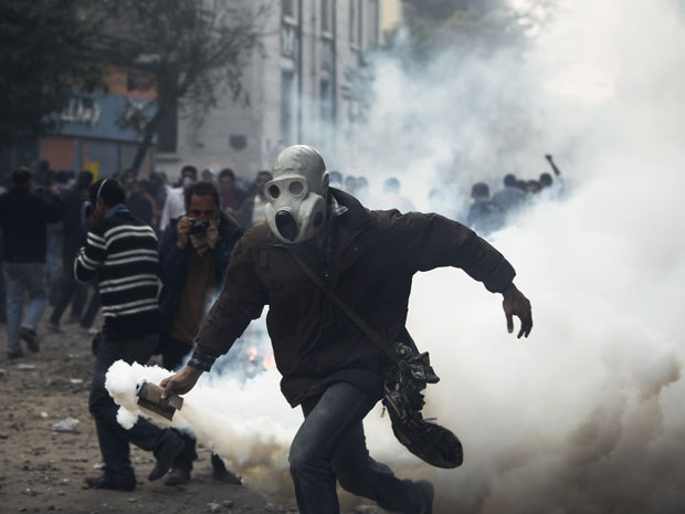 Manifestante egípcio joga lata de gás de volta contra a polícia (Foto: AP Photo/Tara Todras-Whitehill)