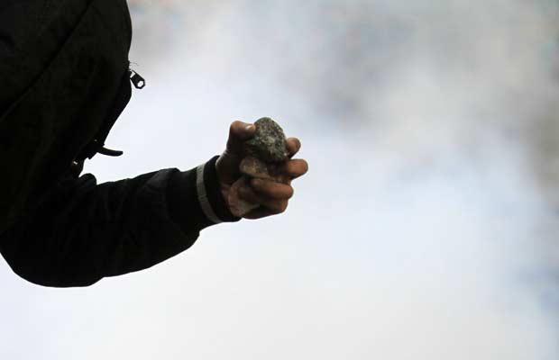 Manifestante joga pedra em policial durante confronto nesta segunda-feira (21) no Cairo (Foto: AP)