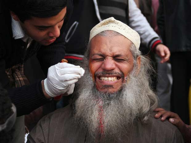 Manifestante ferido é socorrido após confronto nesta segunda-feira (21) no Cairo (Foto: AP)