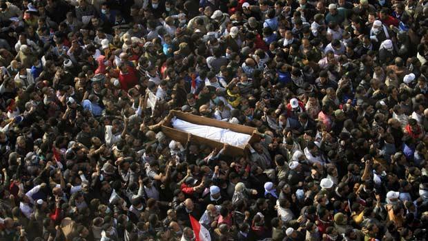 Manifestantes carregam nesta terça-feira (22) corpo de colega morto durante protestos na Praça Tahrir, no Cairo (Foto: AP)