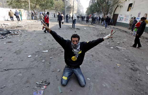 Manifestante faz sinal da vitória durante protestos nesta terça-feira (22) no Cairo (Foto: AP)