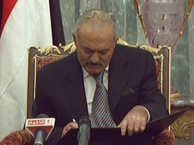Imagem da TV estatal saudita mostra o momento em que Ali Abdullah Saleh assina acordo para deixar o poder no Iêmen nesta quarta-feira (23) (Foto: AFP)