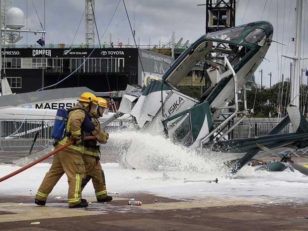 Bombeiros trabalham na aeronave que se partiu ao meio após a queda. (Foto: New Zealand Herald / Sarah Ivey / AP Photo)