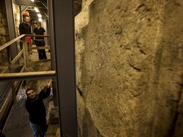 Arqueólogo israelense Eli Shukron, à esquerda, mais abaixo, mostra onde foram achadas as moedas (Foto: AP Photo/Sebastian Scheiner)