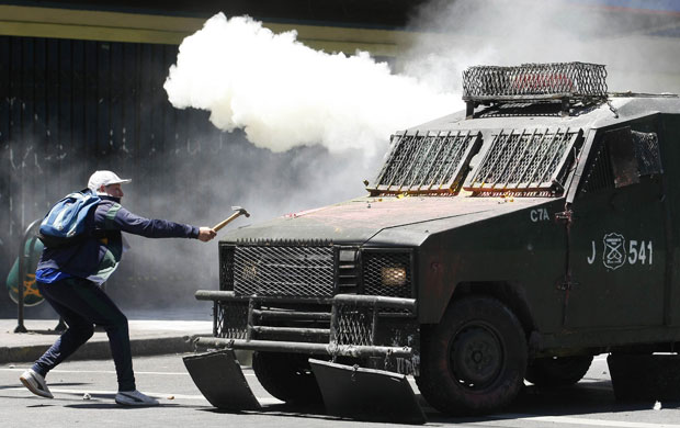 Jovem usa martelo contra um blindado da polícia em Santiago (Foto: Eliseo Fernandez/Reuters)