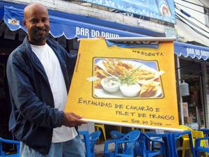 David mostra o cartaz de seu bar, terceiro vencedor do concurso Comida di Buteco (Foto: Bernarado Tabak/G1)