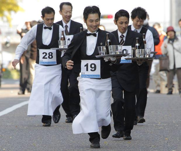 Garçons carregavam bandejas com bebida e copos. (Foto: Itsuo Inouye/AP)