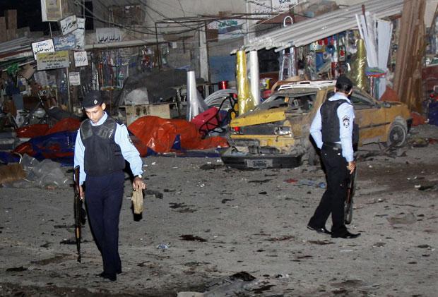 Policiais trabalham no local das explosões no mercado de Basra (Foto: Nabil al-Jurani/AP)