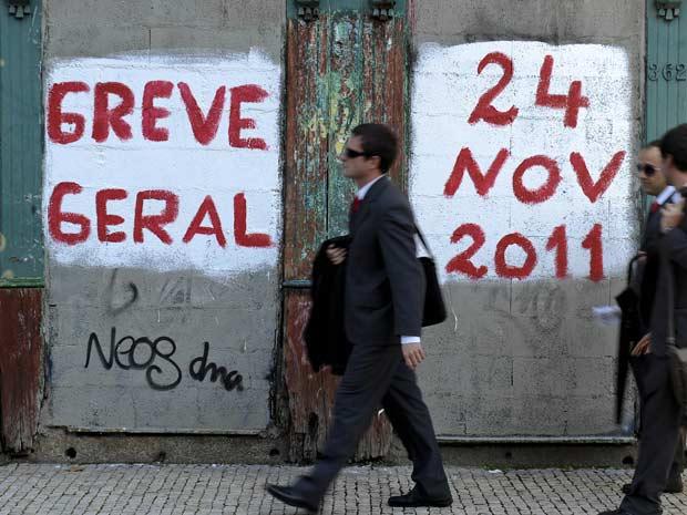 Portugueses passam em frente a muro com apelo à greve nesta quinta-feira (24) em Lisboa (Foto: AP)