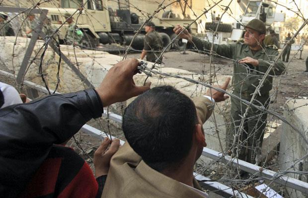 Membro das forças de segurança fala com manifestantes em barreira que protege o ministério do Interior, ao redor da praça Tahrir, nsta quinta (Foto: Esam Al-Fetori/Reuters)