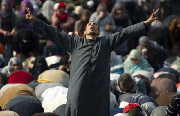 Manifestante faz sinal da vitória após as rezas na praça Tahrir, nesta sexta (25) (Foto: Odd Andersen/AFP)