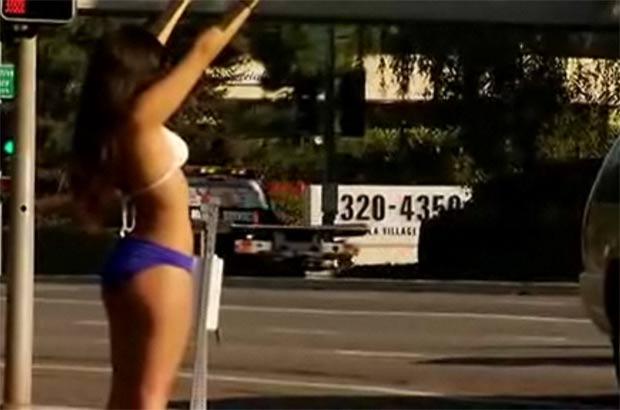 Arlene Mossa Corona foi filmada usando biquíni e salto alto enquanto segurava cartaz. (Foto: Reprodução)