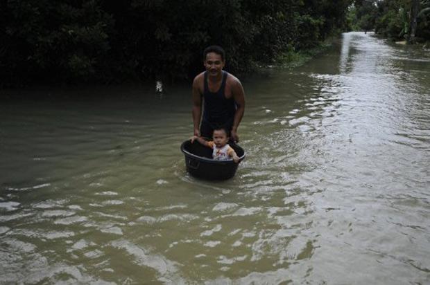 Homem conduz criança em bacia em meio a área inundada na província tailandesa de Narathiwat, nesta sexta (25)  (Foto: Madaree Tohlala / AFP)